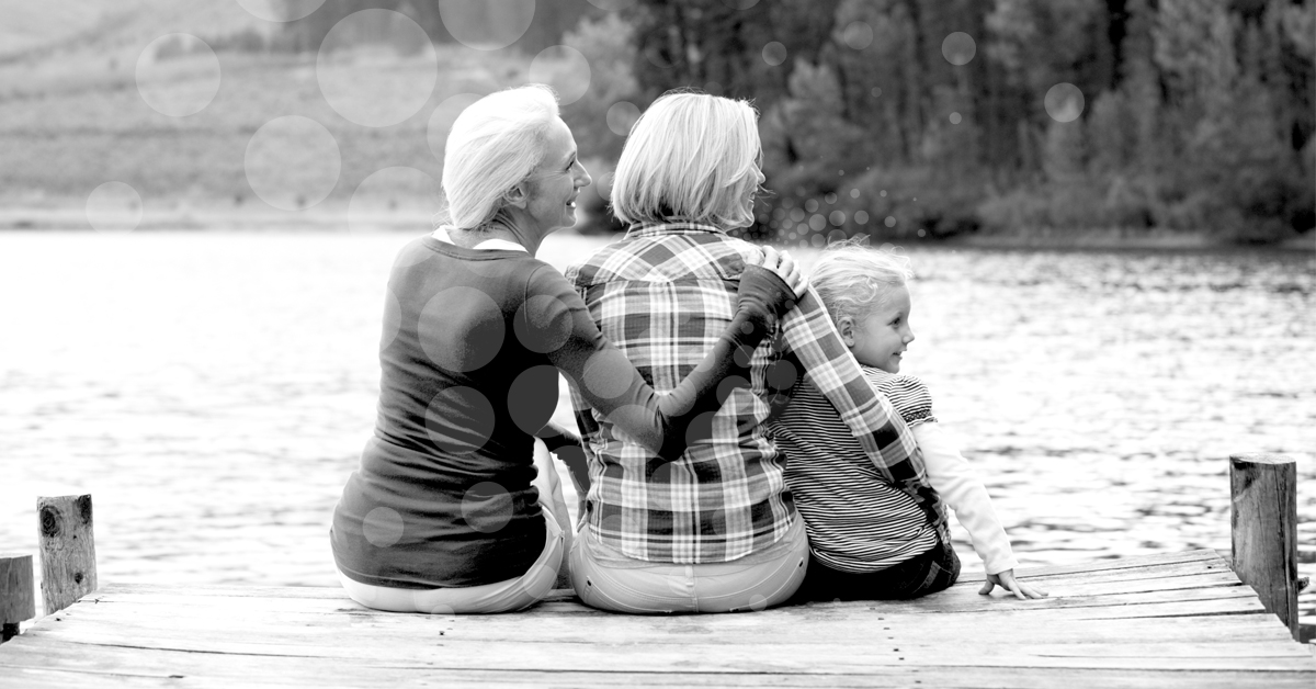 Three generations of women in family sitting on pier