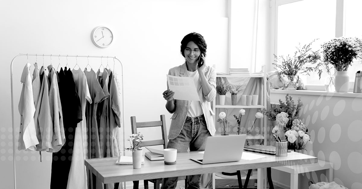 Entrepreneurial woman looks at paper statement while talking on the phone about her small business.